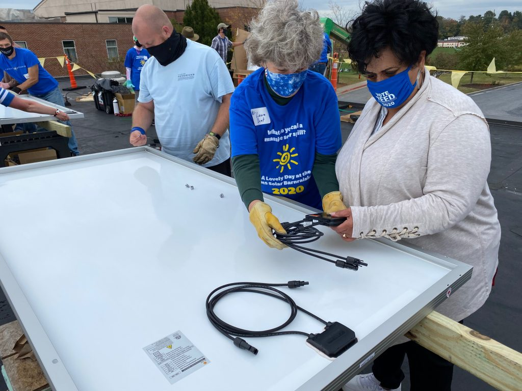 Mayor of Harrisonburg Deanna Reed assisting volunteers with installation.